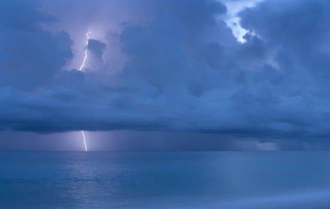 Lightning strikes over the ocean at Midtown Beach on Oct. 16 in Palm Beach. GREG LOVETT / THE PALM BEACH POST