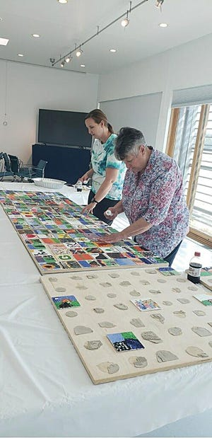 Stacey Barnes and Ann Dixon assemble tiles painted by members of the community in conjunction with the upcoming CROSSROADS: Change in Rural America exhibit from the Smithsonian Institution.