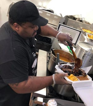 "Ta Bon Fry & Southern Eats Owner and Chef Antonio ""Tony"" Tabon pours his original barbecue sauce over an order of St. Louis Ribs on October 14, 2020."