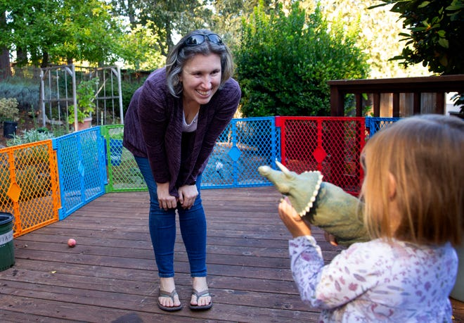 Amanda Thomas plays with her daughter in the backyard of their Eugene home. The family created a safe play space on the deck and made other adjustments as they recover from COVID-19.