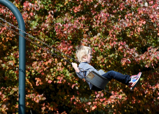Lucas Winters, 4, of Perry Township, gets a push on the swing from his mother, Alexis Winters, as the two enjoyed part of Friday afternoon at Sippo Lake Park. Many folks in Stark County have been outside this week taking in the fall foliage.