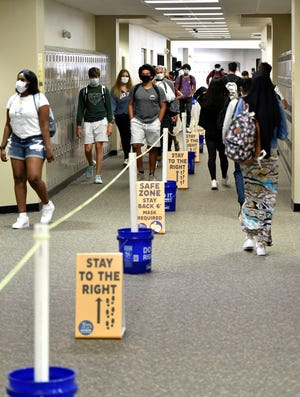 Social distancing is highly enforced at Booker High School in Sarasota, where students are shown changing classes during a recent school day.