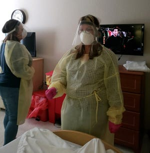 Leonora DeCerio photographed her daughter, Erika Sharer, and sister, Anna Marie Sweets, wearing personal protective gear when they were allowed to visit their mother, Joan Ann DeCerio, as she was at the end of her life on May 7 at Tarpon Point Nursing and Rehabilitation in Sarasota. She passed away the next day.
