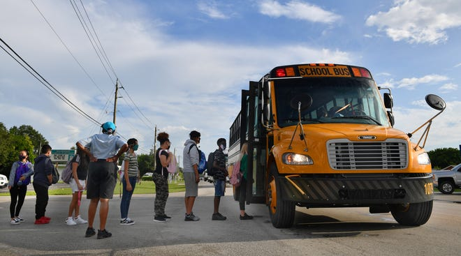 Martha B. King Middle School students line up to board a school bus on the first day of classes in Manatee County. A school district employee got off the bus to make sure everyone was wearing a face mask before boarding the bus. [Herald-Tribune staff photo / Mike Lang]