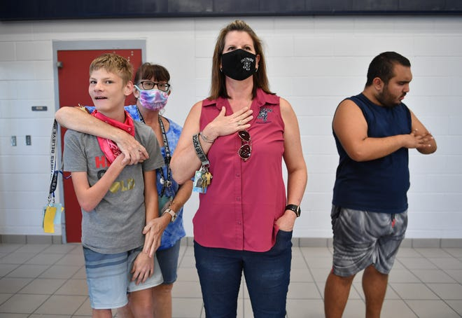 Students Cody Walker, left, and Armando Avich, right, stand for the Pledge of Allegiance with paraprofessional Jane Jansson, second from left, and principal Jamie Lowicz, center, at Oak Park School in Sarasota on Oct. 8.
