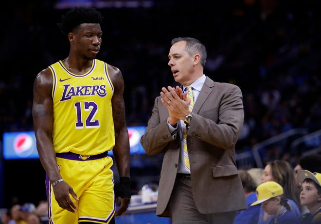Los Angeles Lakers' Devontae Cacok, left, listens to coach Frank Vogel during the first half of the team's preseason game against the Golden State Warriors in 2019. Cacok and the Lakers just clinched the NBA title Sunday by beating the Miami Heat 4-2. (AP Photo/Ben Margot)