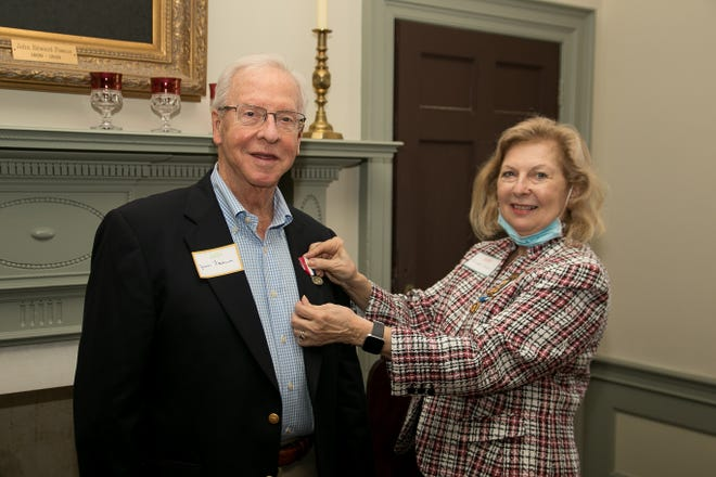 Jim Foscue, owner of Foscue Plantation in Pollocksville, receives the Historic Preservation Medal, awarded by the National Society of the Daughters of the American Revolution. Pinning him is DAR member and Foscue Plantation board member Linda Gill. [Bill Hand / Sun Journal Staff]