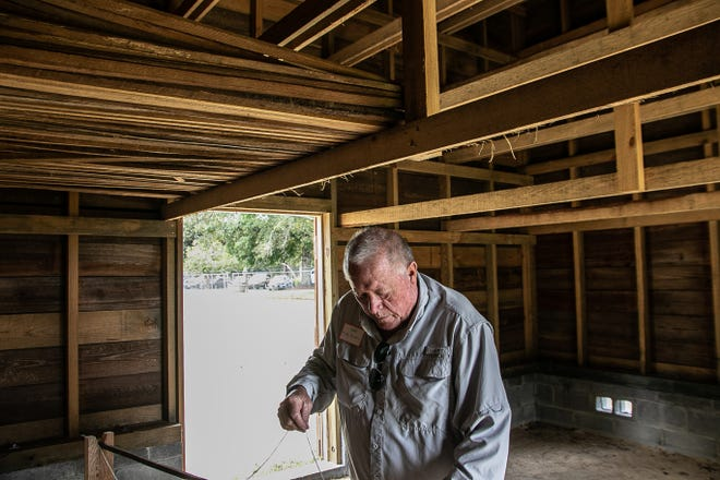 Mike Parker, who oversaw the restoration of the tobacco barn, stands beneath the hanging racks. [Bill Hand / Sun Journal Staff]