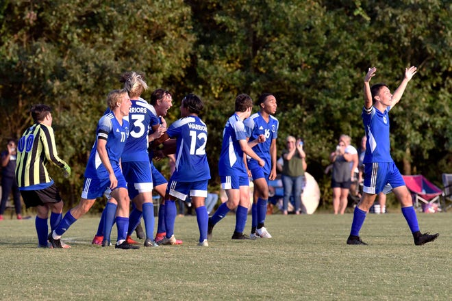 Jack Allen, right, leads the cheers for Fayetteville Christian after making a penalty kick late in Thursday's game as the Warriors defeated Freedom Christian to claim their first NCISAA Sandhills 2-A Conference tournament title.