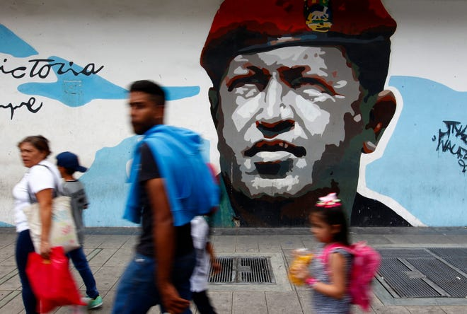 Pedestrians walk past a mural depicting the late President Hugo Chavez, in Caracas, Venezuela, in 2019.