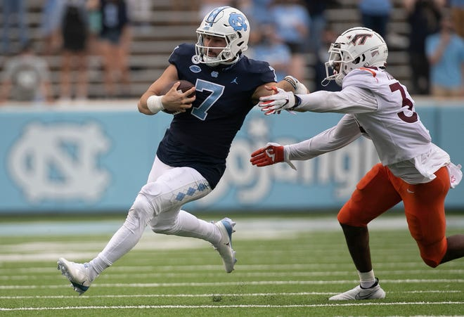 North Carolina quarterback Sam Howell, left, tries to elude Virginia Tech linebacker Alan Tisdale last week.
