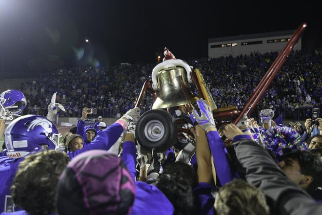 The Pueblo Central High School football team hoists the Bell after defeating Pueblo Centennial on Oct. 25, 2019, in the 71st annual Bell Game at Dutch Clark Stadium.