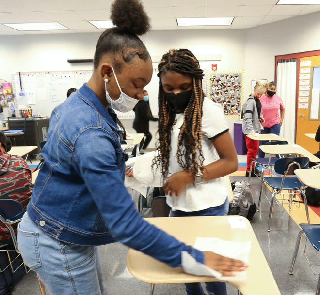 The 2020 school year has presented difficult challenges for teachers in Tuscaloosa City and Tuscaloosa County school systems. Aniyah Wilson and Camiyah Brifford help their teacher, Haleigh Junkin, by cleaning desks at Davis-Emerson Middle School Oct. 13, 2020. Teachers have to ensure the classrooms are cleaned after each period. [Staff Photo/Gary Cosby Jr.]