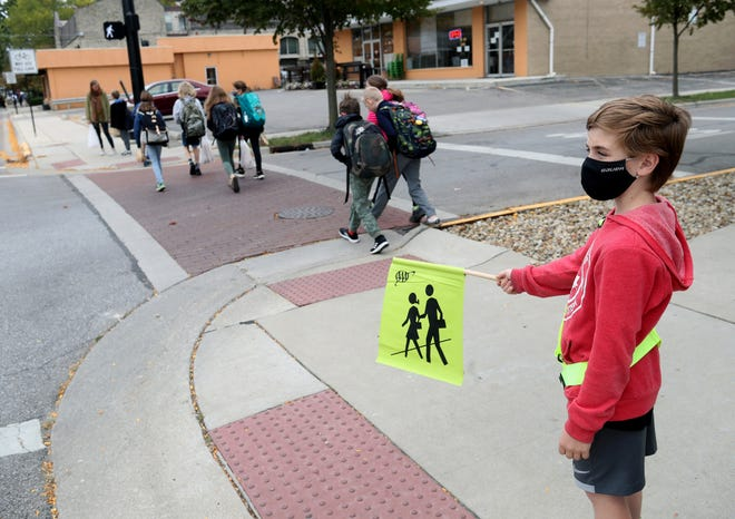 Owen Bentley, 11, guides fellow Edison Intermediate/Larson Middle School students across Oakland Avenue in Grandview Heights on Oct. 15. Owen is part of the school's safety patrol that was created to assist the city with its shortage of crossing guards.