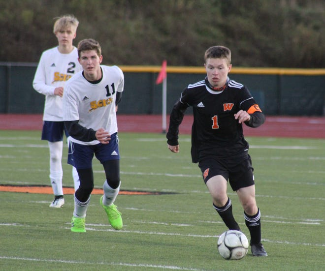 Wellsville senior Alex Ordiway pushes the pace as Scio's Ayden Faulkner (11) pursues Friday night.
