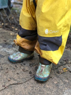 A child in rain pants and boots at the Asheville Waldorf School