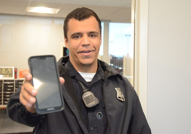 Battle Creek Police Officer Tylon Dilling holds the phone which acts as a camera when placed in a sleeve of his shirt. The lens for the camera is just below the radio microphone. Battle Creek police are seeking approval to purchase body cameras for the officers.