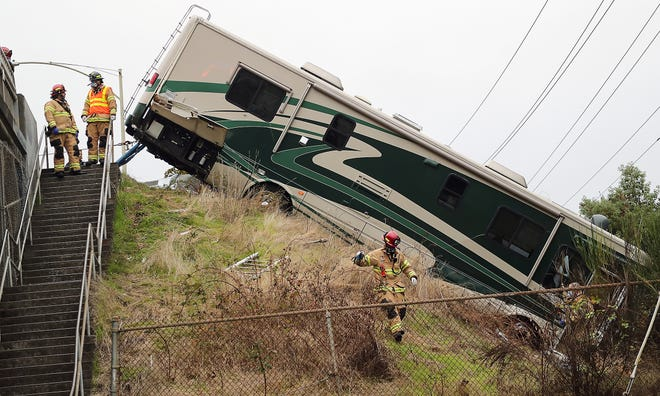 Bremerton Firefighters and paramedics work the scene of an RV that left the roadway and ended up down the embankment on Wheaton Way just north of the bridge on Friday, October 16, 2020.