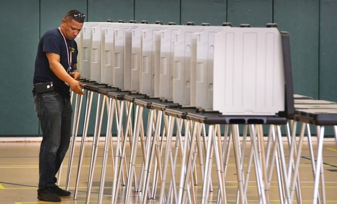 Ray Santiago straightens a row of voting booths at Viera Regional Community Center on Friday. Brevard County Supervisor of Elections workers have been busy all week setting up 10 early voting sites around the county.