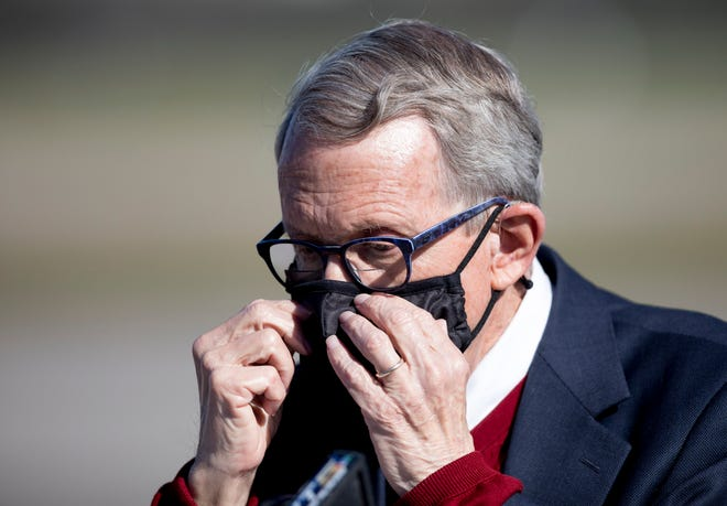 Ohio Gov. Mike DeWine puts his mask back on during a press conference on the rising COVID-19 numbers in Ohio on Friday, Oct. 16, 2020, at Lunken Airport in Cincinnati. The press conference came after record number of cases being reported in Ohio of 2,039 new cases on Wednesday, 2,178 on Thursday and 2,148 on Friday.