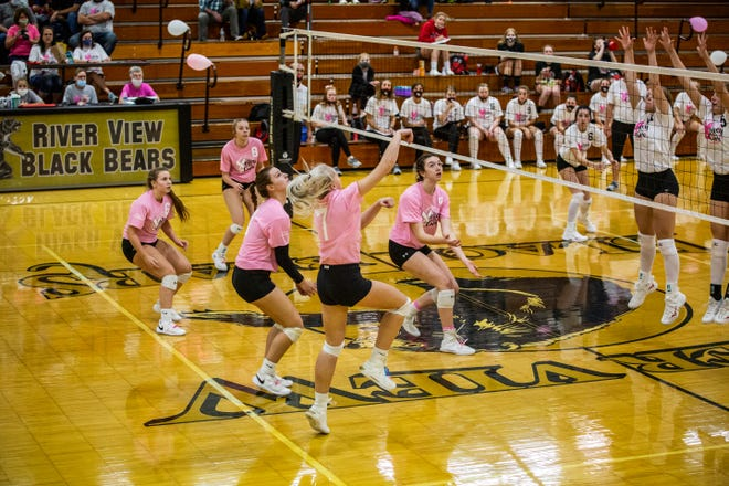 "River View's Carolyn Cox sends the ball over  the block of a couple Lady Redskins during Thursday nights ""Volley for the Cure""  volleyball match."