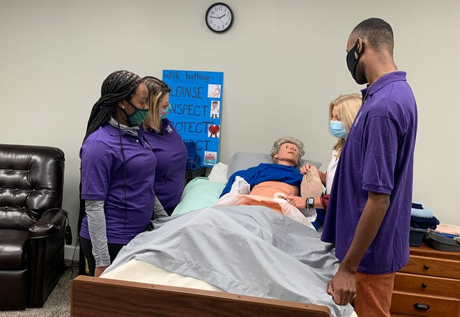 Caregivers participate in their mandatory skills training in the Home Instead training lab with R.N. Kim Marsh before they go to their first shift.