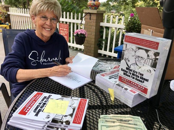 Patty Saalman signs copies of son Scott Saalman's book