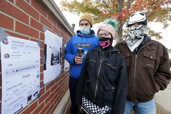 From left Nathan Peet, Hannah Gittings, Anthony Huber's girlfriend; Chris McNeal, and another protester tape hateful social media posts they found on the internet at 61st Avenue and Sheridan Road in Kenosha, Friday, October 16, 2020. They have sued Facebook, along with Kyle Rittenhouse and two men. over trauma they say they suffered. They taped up some of the hateful posts they say led to the violence, and say Facebook allowed such messages to stay on its site.