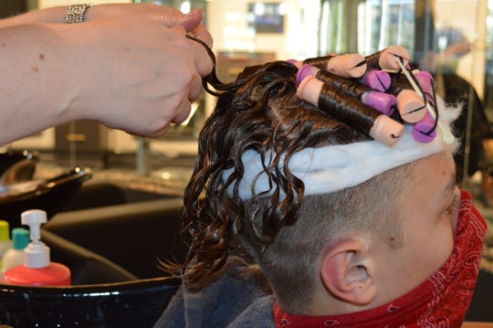 Spargo Salon & Spa hairstylist Hailey Van Hulst removes perm rods from Connor Macleod's hair.