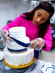 Dee Dee Crenshaw, owner of Cakeology cake shop in Montgomery, Ala., decorates a cake at the shop on Friday October 16, 2020.