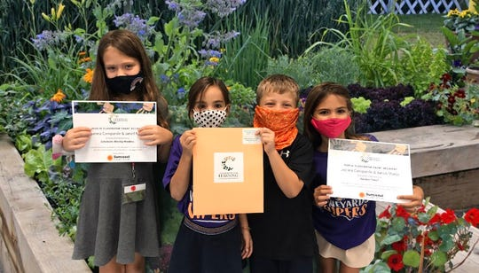 Vineyards Elementary first-grade students from the classrooms of Joanna Campanile and Janell Matos hold up their teachers' grants on Friday, Oct. 16, 2020.