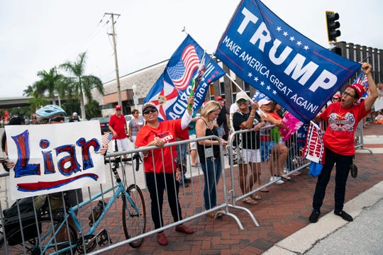 """Kathy Hudson, left, holds a sign that says """"Liar"""" while Alba Williams, center, and Carmen Turner, right, hold up Trump flags as a crowd gathers before a Trump event at the Caloosa Sound Convention Center and Ampitheater in Fort Myers on Friday, October 16, 2020."""
