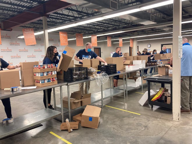 Feeding South Dakota Volunteers package food to be distrusted to local resident on Friday at the Feeding South Dakota headquarters in Sioux Falls. Sanford Health announced Friday that it was donating $1 million to the food bank.