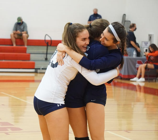 St. Edward's Meredith Burgoon (left) and Miranda Morey (right) hug Alexa Soderman after the Pirates won their first district championship in 17 years with a sweep of Merritt Island Christian on Thursday, Oct. 15, 2020.