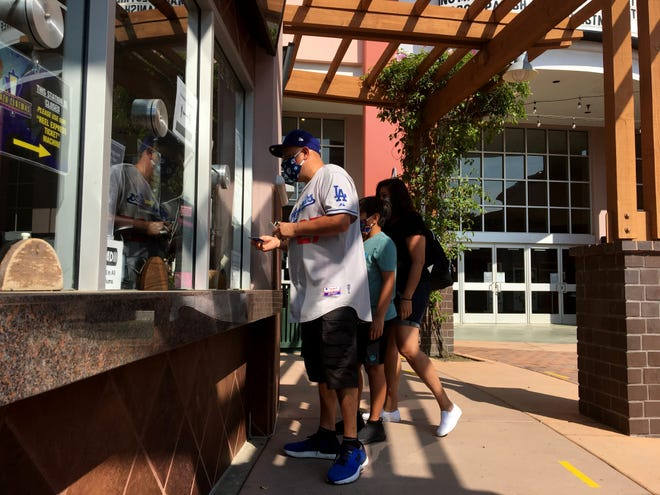 """Joey Velasco, 48, of Oxnard, Trish Rodriguez and 10-year-old Brandon Velasco are the first to arrive at Oxnard's Plaza Cinema 14 movie theater on Friday, Oct. 16, 2020, to watch """"Honest Thief"""" as theaters across the county reopen."""