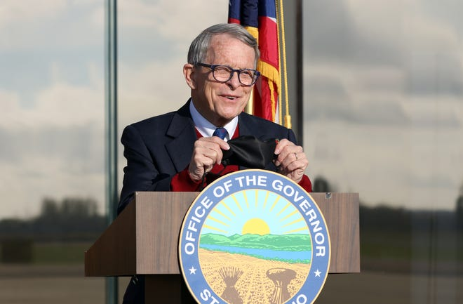 """This is our ticket to freedom,"" Ohio Gov. Mike DeWine said while holding up his mask Friday during an appearance at Zanesville Municipal Airport on Friday."