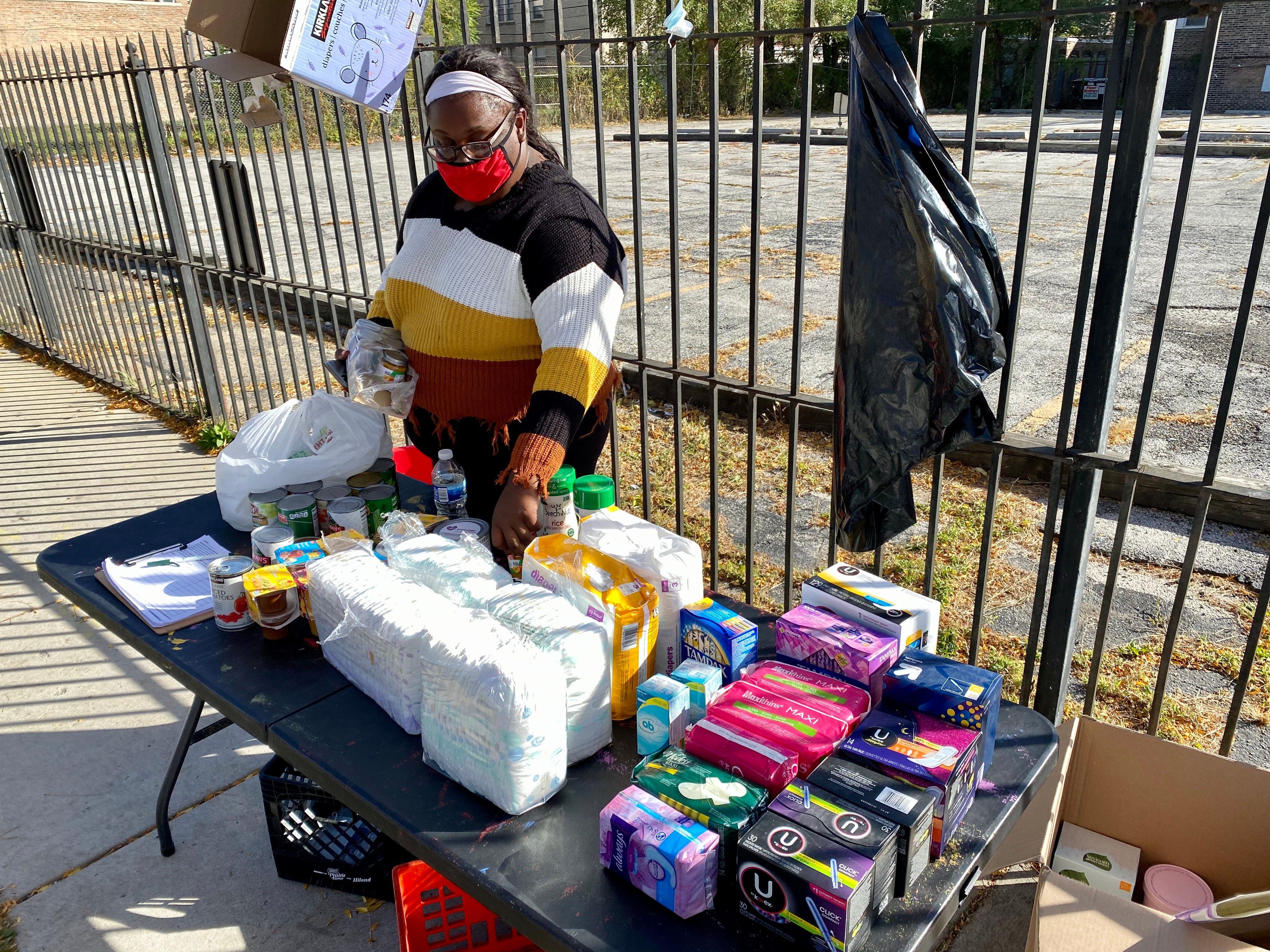 Juanita Tennyson, 23, gives out donated food and household supplies in the South Shore neighborhood on the South Side of Chicago on  Oct. 14., 2020.