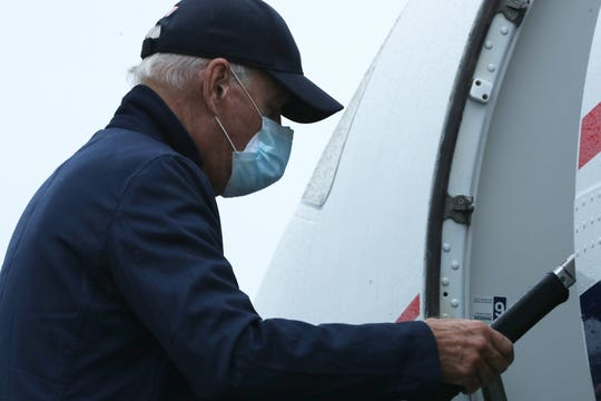 Wearing two face masks to reduce the risk posed by the coronavirus, Democratic presidential nominee Joe Biden boards a flight to Michigan at New Castle County Airport October 16, 2020 in New Castle, Delaware.