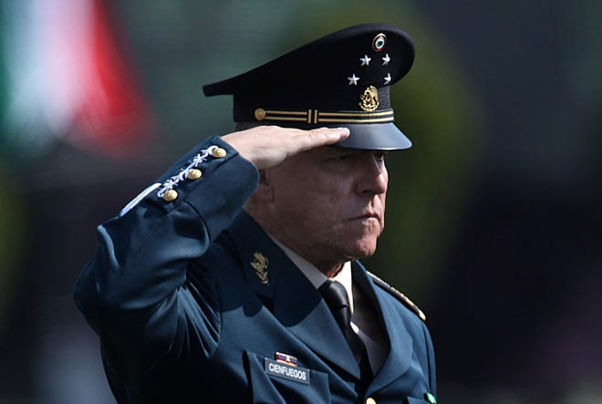 In this April 16, 2016, file photo, Mexico's Defense Secretary Gen. Salvador Cienfuegos Zepeda salutes soldiers at the Number 1 military camp in Mexico City.