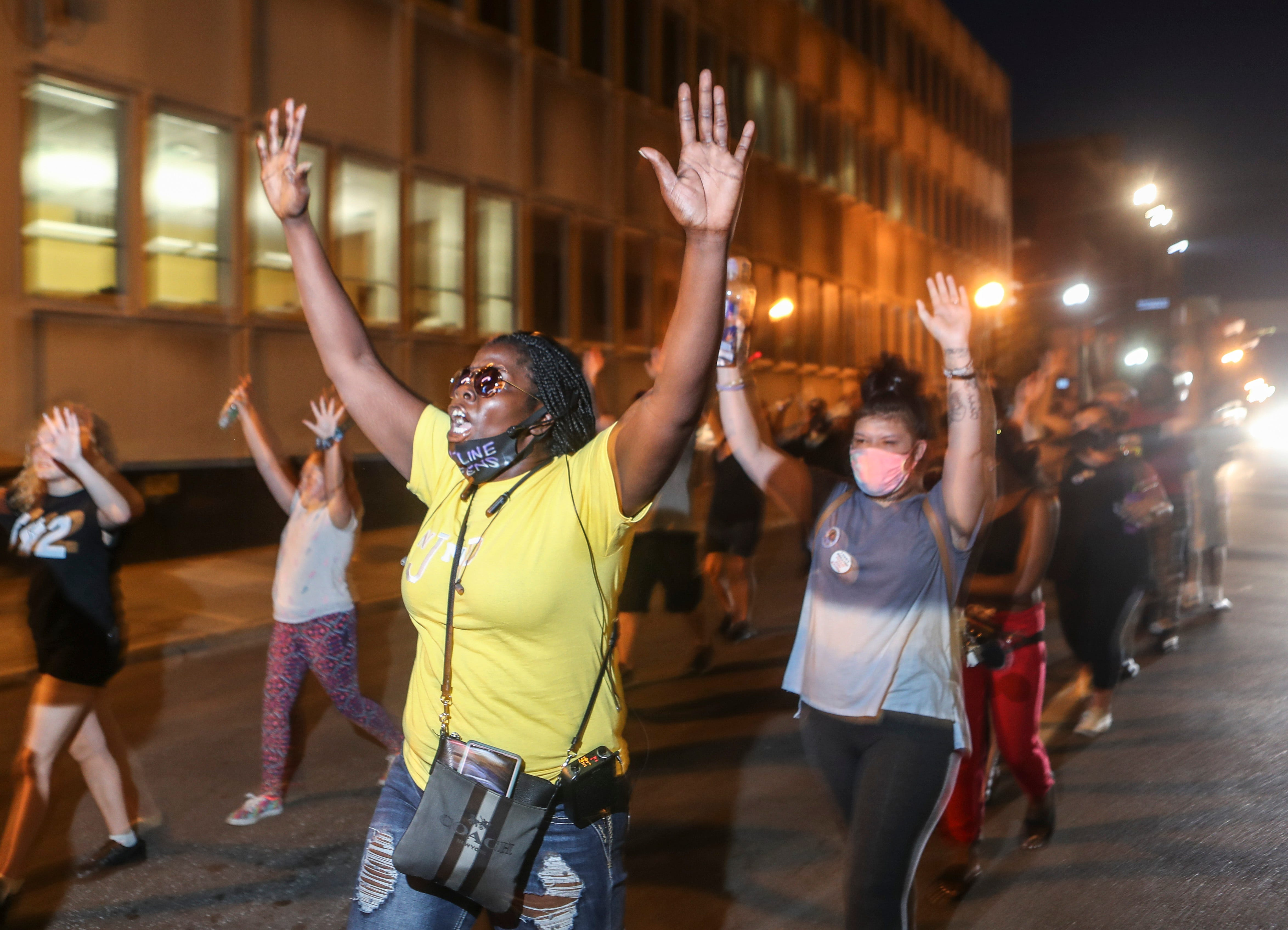 Demonstrators raise their hands during a peaceful protest on July 31, 2020 demanding justice for the murder of Breonna Taylor. Chants of 'Say her name...Breonna Taylor' as well as 'David McAtee' and 'Tyler Gerth' could be heard in the downtown streets of Louisville at night.