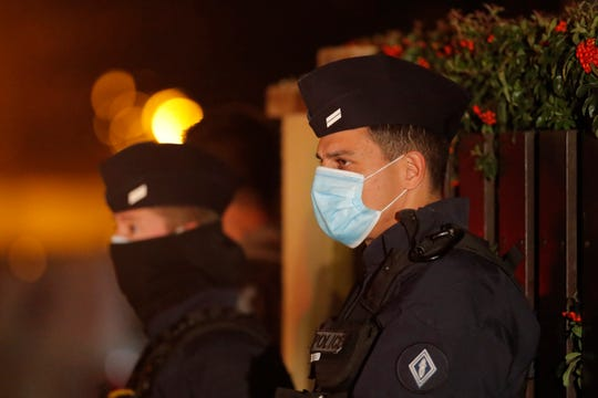 French police officers are standing outside a high school after a history teacher opened a discussion with students on the cartoons of the Prophet of Islam Muhammad beheaded, October 16, 2020 Conflans-Sainte-Honorine, north of Paris.