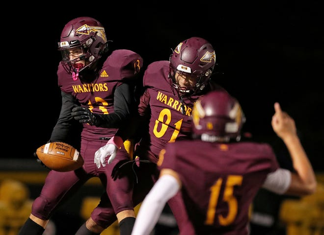 Walsh Jesuit receiver Dom Grguric, left, celebrates with Kenyon Marshall, center, and Matt Natale after a touchdown reception during the second half of a Division II playoff game against the Garfield Heights Bulldogs, Friday, Oct. 16, 2020, in Cuyahoga Falls, Ohio. [Jeff Lange/Beacon Journal]