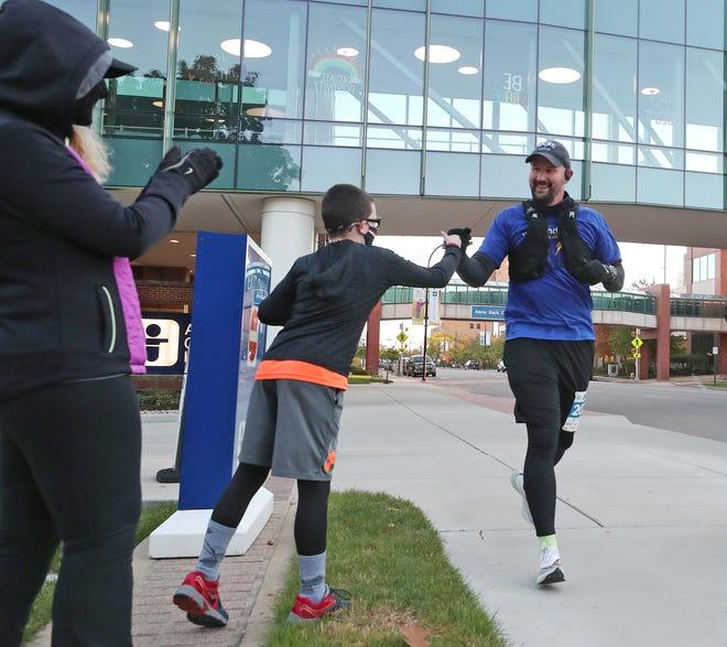 Kolt Codner fist-bumps with nephew Landon Lanham as Codner's sister Kelsey Lanham cheers him on Saturday during his virtual marathon around Akron Children's Hospital.