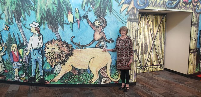Smith stands by a mural near the children's library. Though she has held many positions throughout her career, she spent 30 years as a children's librarian.