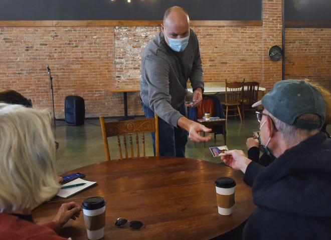 "Democratic Iowa-4th congressional district candidate JD Scholten distributes his baseball card during the "" Coffee with the Candidate"" event at Farm Ground Coffee Saturday, Oct. 17, 2020, in Nevada, Iowa."