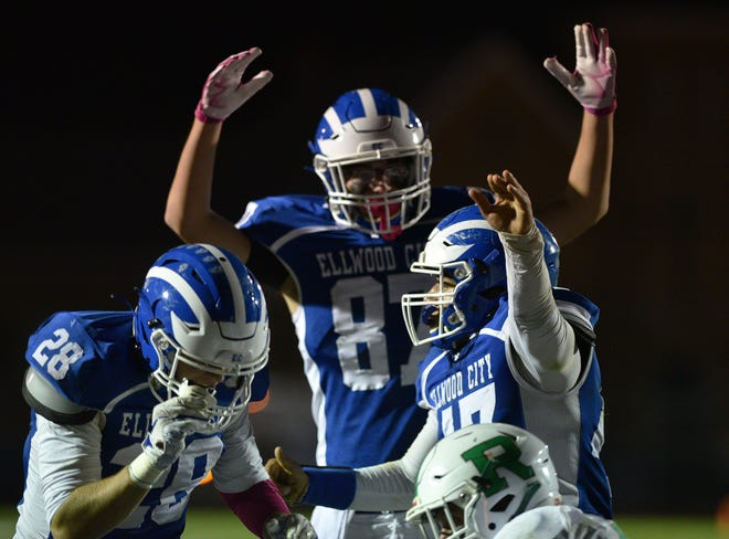 Ellwood City players Sammy DiCaprio (28), Aaron Hobel (87) and Brighton Mariacher (17) celebrate their first touchdown of the night against Riverside at Helling Stadium.