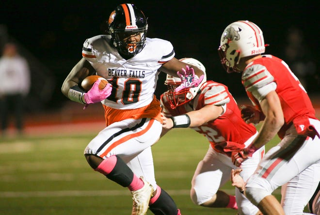 Beaver Falls Joshua Hough (10) attempts to shake Freedom's Jimmy Happ (52) and Reiker Welling (5) during the second half Friday night at Freedom Area High School.