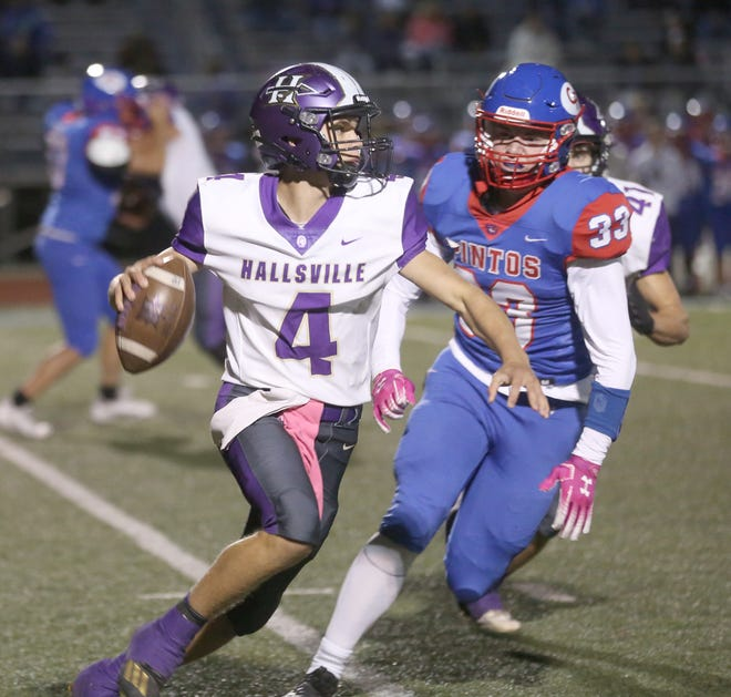 Hallsville junior quarterback Tyger Cobb (4) rolls out to his right to throw a pass in the first half Friday night against California in Tri-County Conference action at California High School.