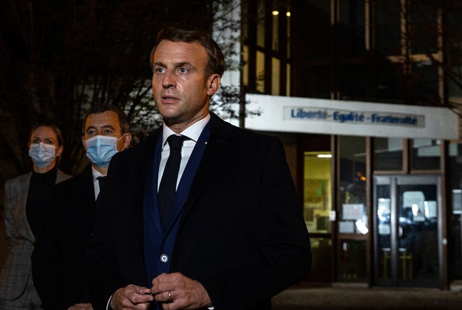 French President Emmanuel Macron, flanked by French Interior Minister Gerald Darmanin, second left, speaks in front of a high school Friday Oct.16, 2020 in Conflans Sainte-Honorine, northwest of Paris, after a history teacher who opened a discussion with high school students on caricatures of Islam's Prophet Muhammad was beheaded.