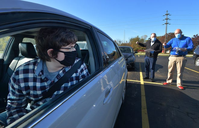 Erie resident Michael Sherman, 26, left, waits as AirBorn Inc. supervisors Adam Wray, back left, and Kyle Kleinedler discuss job candidates and qualifications during a drive-through job fair at AirBorn on Saturday in Lake City. Sherman is looking for a shorter commute compared to his current job in Jamestown, N.Y.